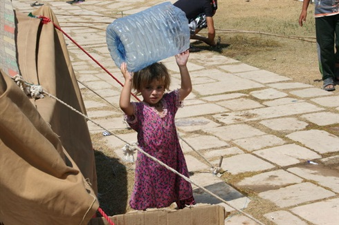 Iraq: refugee camp - a small girl collects the family's water supply