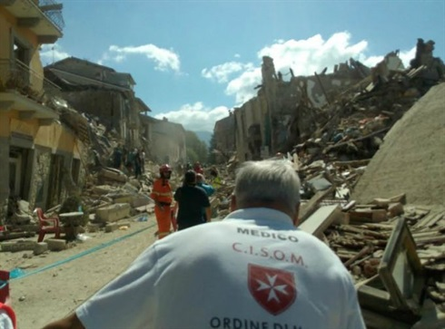 Amatrice - a medico from the Italian Relief Corps of the Order Malta surveys the ruins of the little town