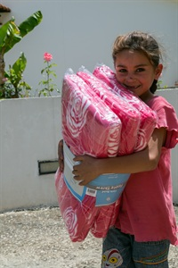 A small Syrian collects blankets for her refugee family, Khaldieh centre, north Lebanon Photo: Andreas Krogmann
