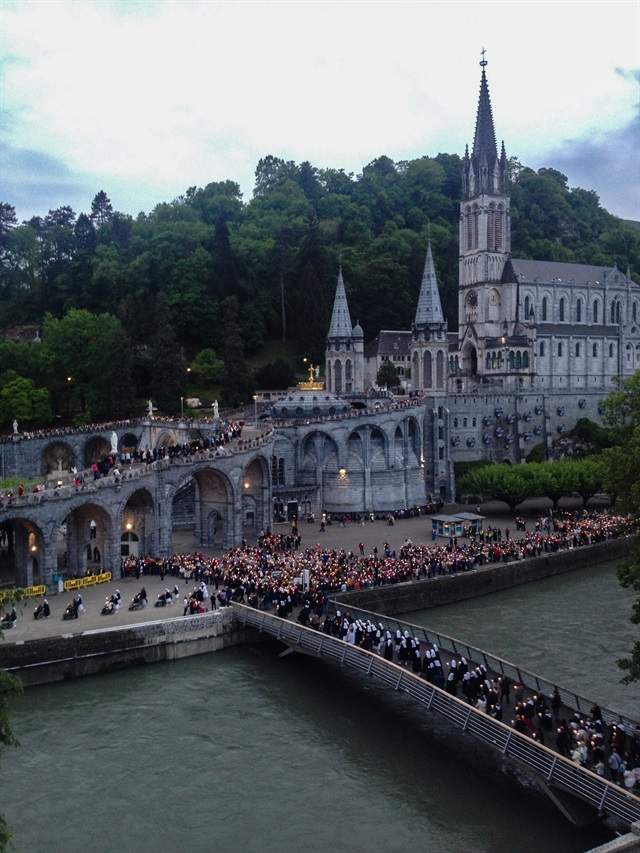 Lourdes the Order processes at dusk